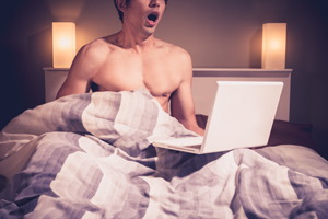 Young man is sitting in bed and watching masturbating laptop